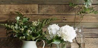 kvety vo vázach položené na drevenom stole, v pozadí s dreveným obkladom na stenu