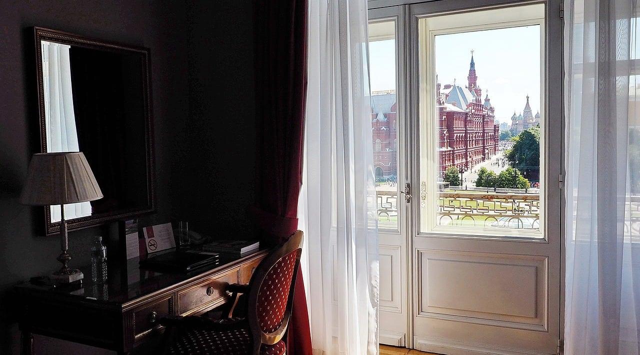 calunena-stolicka-vitage-stolik-vyrezavane-zrkadlo-dlhe-zavesy-vyhlad-z-okna-biele-drevene-dvere-na-balkon-starozitna-lampa