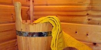 drevený kýbel s drevenou varechou a uterákom položený na dreve v saune