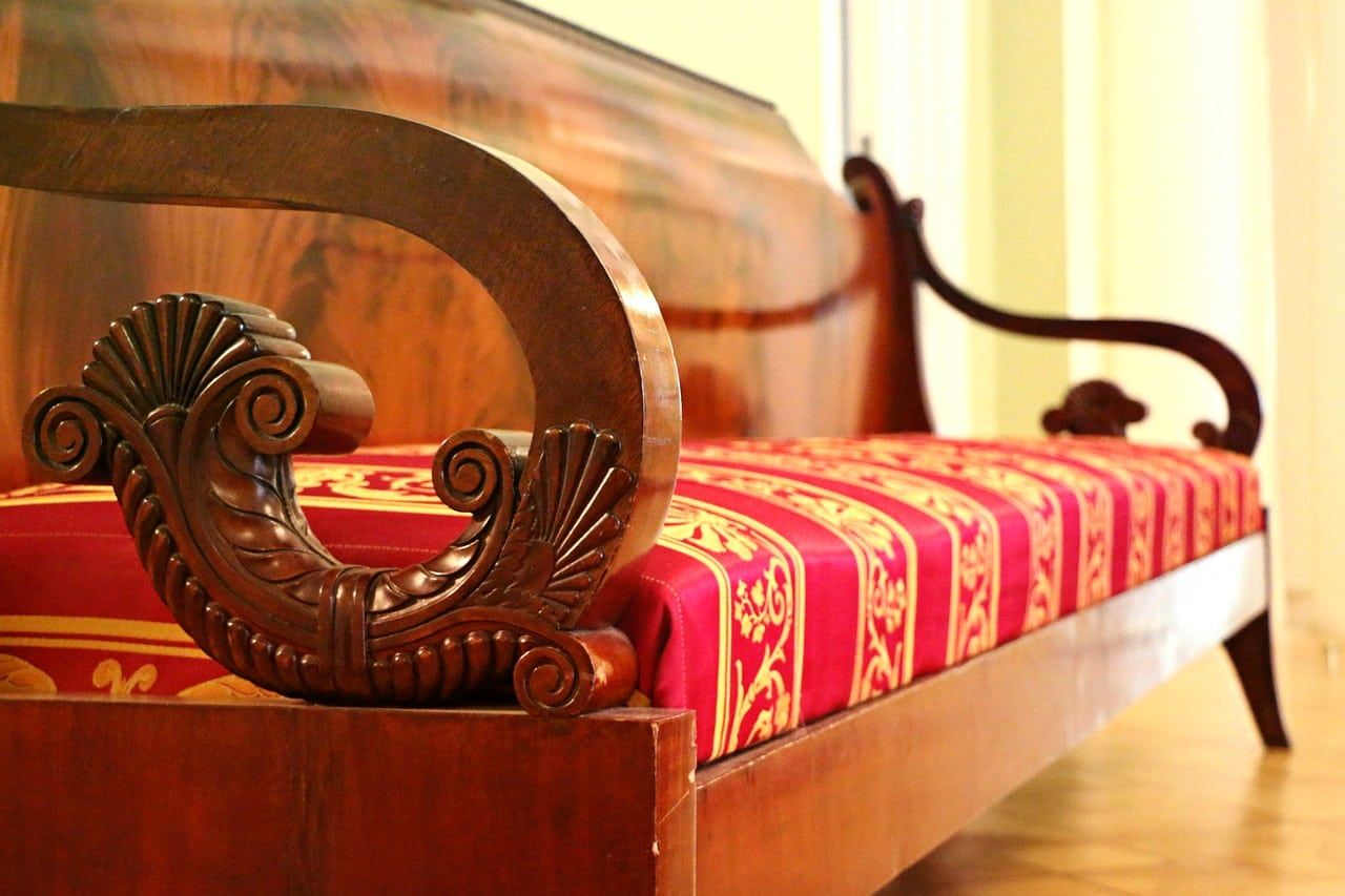 vintage-lavica-s-vyrezavanymi-drevenymi-ornamentmi-a-cervenym-vankusom