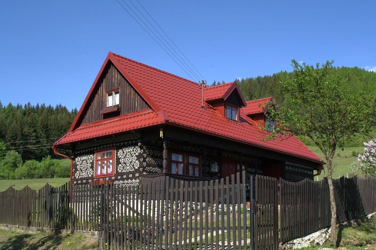 dreveny-dom-s-cervenou-strechou-drevene-okna-okenice-zdobenie-bielym-vapnom-dreveny-plot