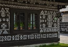 dreveny-domcek-zdobeny-bielymi-ornamentmi-okno-kvetiny-cicmany