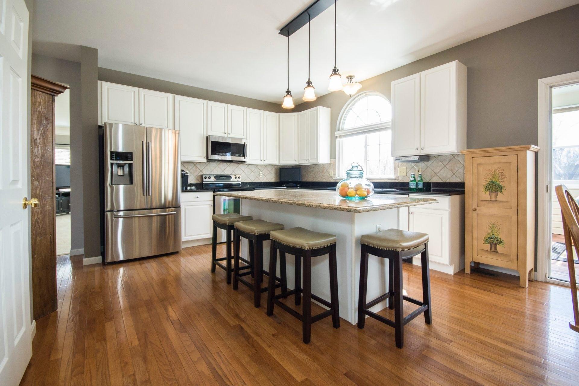 drevena-podlaha-kuchyna-ostrovcek-v-strede-miestnosti-barove-kuchynske-stolicky-lampa-kuchynska-linka-chladnicka-okno