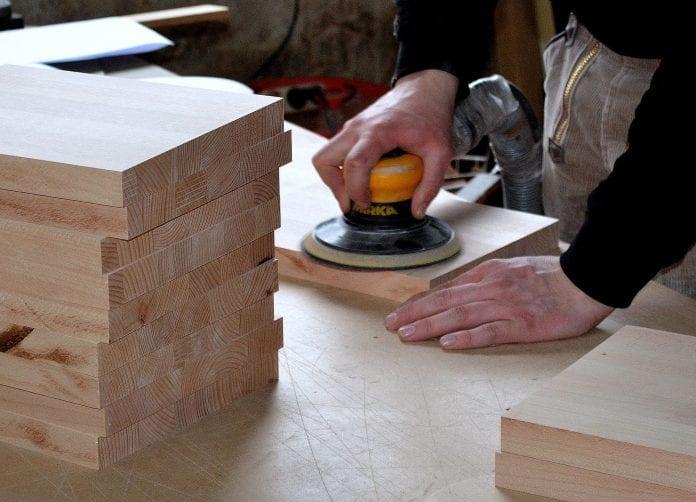 muz-robotnik-stavba-drevene-dosky-bruska-praca-s-drevom-uprava-priprava-natierania